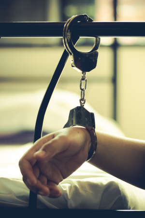 prostitution: Lady with handcuff on bed, Human trafficking - Concept Photo Stock Photo