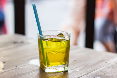 Chrysanthemum iced tea with straw on a wooden table.