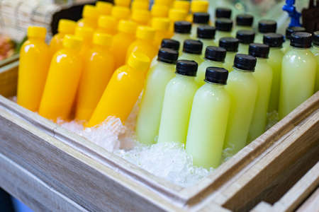 Bottles of fresh juice in a wooden bucket filled with ice.