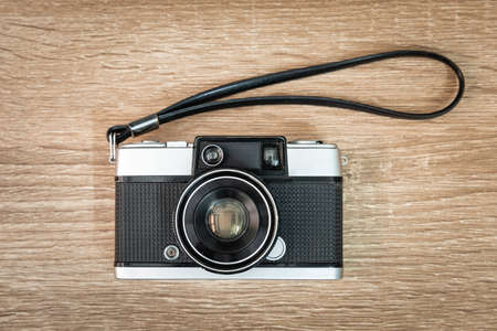 Vintage film camera on wooden table.