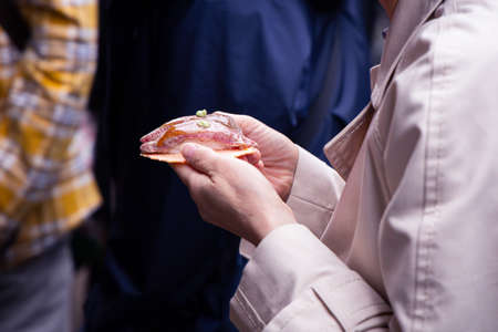 Tourist with Hida beef sushi on rice cracker in Takayama old town, Japan. 写真素材