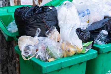 Overflowing garbage bins with household waste