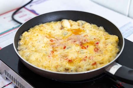 Omelette in frying pan on an induction cooker Stock Photo