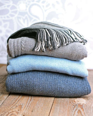 Pile of warm wool clothing lying on a wooden table