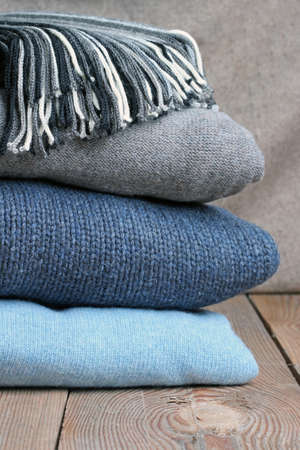Pile of warm wool clothing lying on a wooden table photo