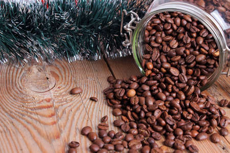 Jar with coffee beans with green garland on a wooden table photo