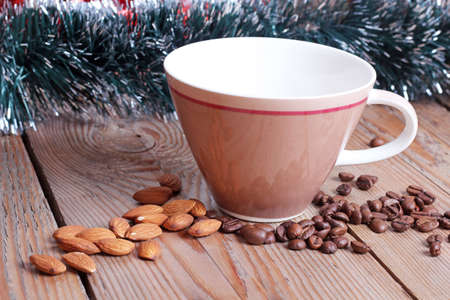 Coffee cup and beans with almond on a wooden table photo
