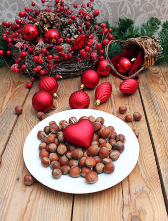 Plate with nuts and christmas hearth with christmas decoration on the background. Selective focus photo