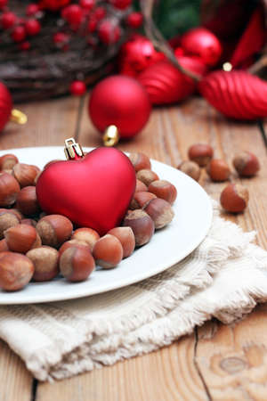 Christmas hearth with nuts on a white plate with Christmas background. Selective focus photo