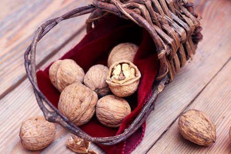 Walnuts in the vintage basket with red napkin. Russian tradition to eat nuts on Christmas holidays. Selective focus photo