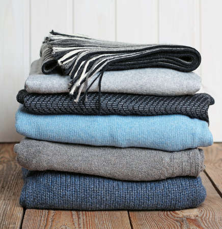 Stack of warm woolen clothing lying on a wooden table photo