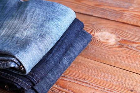 in jeans: Pila de tejanos azules y negros sobre una mesa de madera. Enfoque selectivo. Copiar espacio de fondo