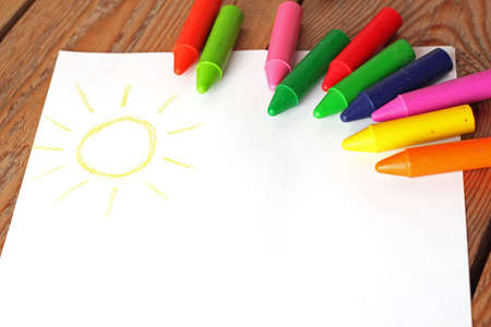 Oil pastel crayons lying on a paper with painted children's drawing. Copy space background. Selective focus