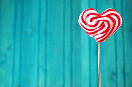 Heart shaped lollipop for Valentines Day with turquoise background. Copy space background Stok Fotoğraf