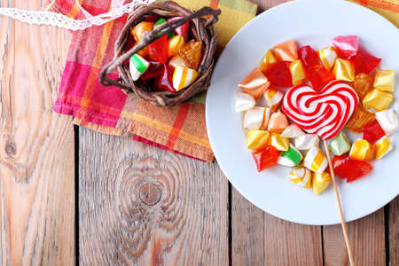 Plate and basket with colorful sweet candies. Copy space background. Selective focus. Traditional Seker Bayram holidays candies 写真素材