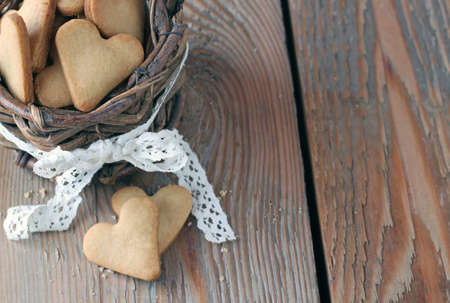 wintery day: Holidays, love, food and drink concept. Handmade heart cookies for Valentines day in a basket on a wooden table in a vintage style. Selective focus