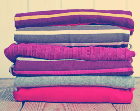 Stack of warm knitting clothing lying on a wooden table. Vintage style, toned image photo