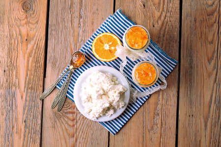 Assortment of breakfast products (homemade yogurt, cottage cheese; orange jam) on a wooden table. Top view, selective focus photo
