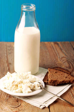 Assortment of diary products for breakfast (homemade cottage cheese; milk) with rye bread on a wooden table. Selective focus photo