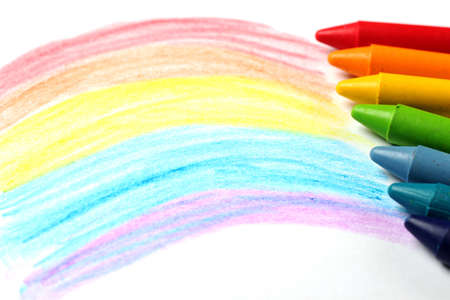 Crayons lying on a paper with children's drawing rainbow. Selective focus, copy space background