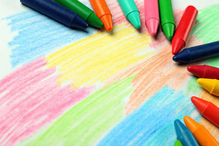 crayons: Crayons lying on an abstract hand drawing background. Selective focus, copy space background Stock Photo