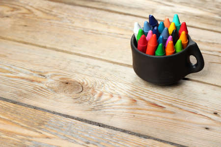 Crayons in a mug on a wooden table. Selective focus, copy space background