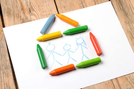 Home, love, family, still life concept. Crayons lying on a paper with children's drawing family. Selective focus, copy space background