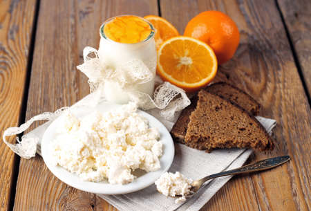 Assortment of breakfast products (homemade yogurt, cottage cheese, orange jam, rye bread) on a wooden table. Selective focus photo