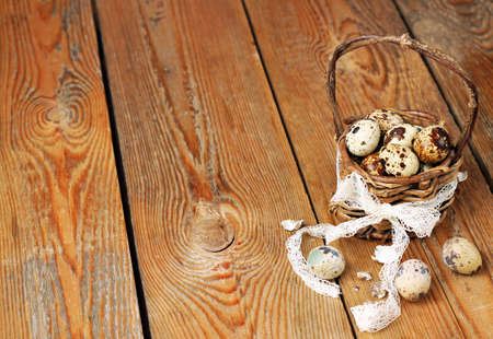 Quail eggs in a basket on a wooden table. Selective focus, easter copy space background photo