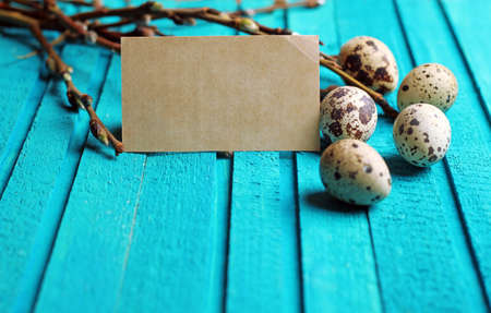 Happy easter concept. Quail eggs and willow branch on a wooden background. Selective focus. Copy  space note photo