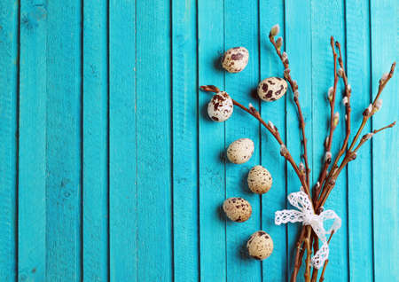 Happy easter concept. Quail eggs and willow branch on a wooden background. Selective focus. Copy  space note Archivio Fotografico