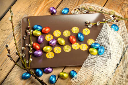 Still life, holidays, food and drink concept. Easter decoration with chocolate eggs and willow branch. Top view, selective focus photo