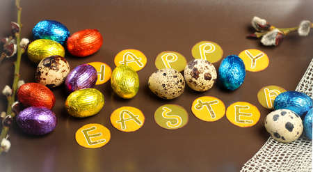 Still life, holidays, food and drink concept. Easter decoration with quail and chocolate eggs and willow branch. photo