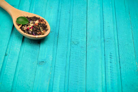 food and drink: Still life, healthcare, food and drink concept. Tea in a spoon on a turquoise wooden table. Selective focus, copy space background Stock Photo
