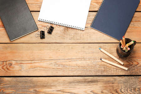 book background: Still life, business, education concept. Office supplies, notepad, diary, staple and pencils on a wooden table. Selective focus, copy space background, top view