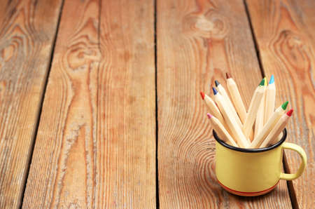 Still life, business, education concept. Pencils in a mug on a wooden table. Selective focus, copy space background