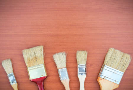 refurbish: Still life, house and garden concept. Paint brushes on a wooden background. Selective focus, copy space background, top view