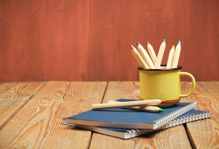 Still life, business, education concept. Pencils in a mug with notepad on a wooden table. Selective focus, copy space background Archivio Fotografico