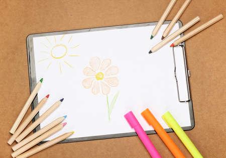 convivencia escolar: La naturaleza muerta, los ni�os, la escuela, el concepto de la educaci�n. Dibujo de flores y el sol con papeler�a, marcadores y l�pices en una mesa. Enfoque selectivo, espacio de copia de fondo, vista desde arriba Foto de archivo
