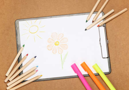 school time: Still life, children, school, education concept. Drawing flower and sun with stationery, markers and pencils on a table. Selective focus, copy space background, top view