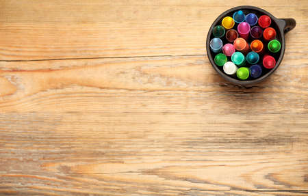 Still life, business, education concept. Crayons in a mug on a wooden table. Selective focus, top view, copy space background