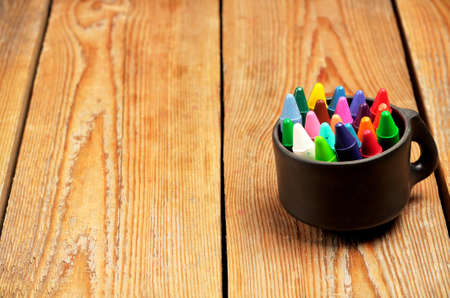 baby hand: Still life, business, education concept. Crayons in a mug on a wooden table. Selective focus, copy space background Stock Photo
