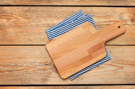 Still life, food and drink concept. Kitchen cooking utensils (cutting board, napkin) on a wooden table. Selective focus, copy space background, top view