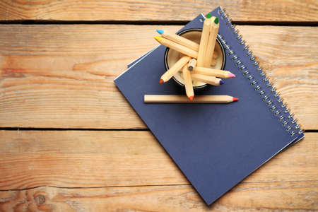 office note: Still life, business, education concept. Pencils in a mug with notepad on a wooden table. Selective focus, copy space background, top view