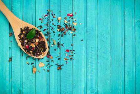 Natürmort, sağlık, gıda ve içecek konsepti. Turkuaz ahşap masada bir kaşık çay. Seçmeli odak, kopya uzay arka plan, üstten görünüm