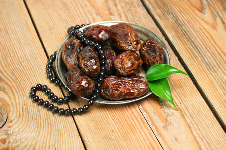dattes: Nature morte, nourriture et boisson, vacances concept. dates et perles du Ramadan sur une table en bois. mise au point sélective Banque d'images