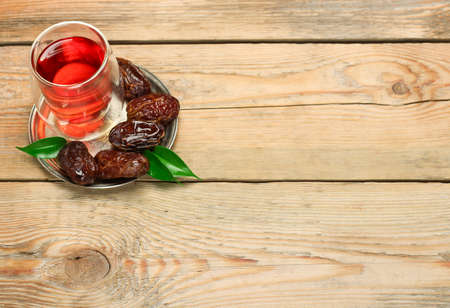 Still life, food and drink, holidays concept. Ramadan dates and tea on a wooden table. Selective focus, copy space background, top view