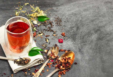 herb tea: Still life, food and drink concept. Various kinds of tea with a glass of tea on a black chalkboard. Selective focus, copy space background. Stock Photo