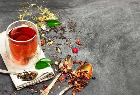 Stilleven, eten en drinken concept. Verschillende soorten thee met een glas thee op een zwart bord. Selectieve aandacht, kopie ruimte achtergrond.