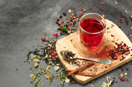 chinese herbs: Still life, food and drink concept. Various kinds of tea with a glass of tea on a black chalkboard. Selective focus, copy space background. Stock Photo